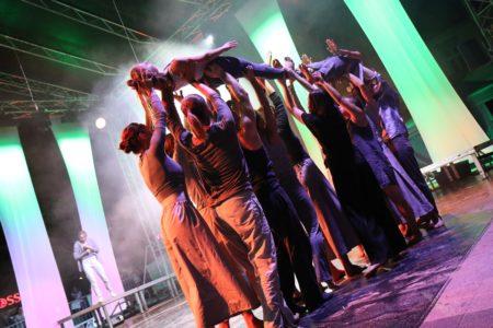 Ludzie podnoszą jedną z sióstr podczas spektaklu SHADES wyreżyserowanego przez Marjon van Grunsven, w projekcie skoordynowanym przez Wojciech Chowaniec.